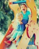 Crianças felizes na corrediça Imagens de Stock