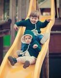 Crianças felizes na corrediça no campo de jogos Fotos de Stock