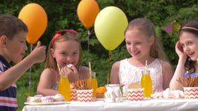 Crianças felizes na festa de anos no jardim do verão filme