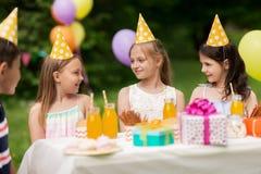 Crianças felizes na festa de anos no jardim do verão fotografia de stock