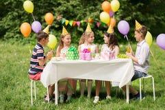 Crianças felizes na festa de anos no jardim do verão foto de stock