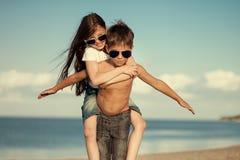 Crianças felizes nos óculos de sol que têm o divertimento no mar Menino e menina Foto de Stock
