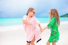 Crianças felizes pequenas que têm muito divertimento na praia tropical que joga junto Meninas adoráveis que dançam na ilha das Ca Imagem de Stock