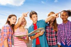 Crianças felizes que apontam com fim da posição do mapa Fotos de Stock