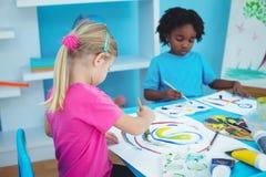 Crianças felizes que apreciam artes e pintura dos ofícios foto de stock royalty free