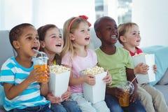 Crianças felizes que apreciam a pipoca e as bebidas ao sentar-se imagem de stock
