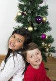 Crianças felizes que colocam sob a árvore de Natal Foto de Stock