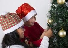 Crianças felizes que colocam sob a árvore de Natal Imagens de Stock