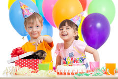 Crianças felizes que comemoram a festa de anos com caixa de presente da abertura Imagem de Stock