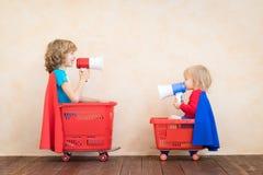 Crianças felizes que conduzem o carro do brinquedo em casa imagem de stock