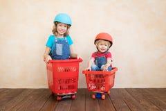 Crianças felizes que conduzem o carro do brinquedo em casa imagens de stock