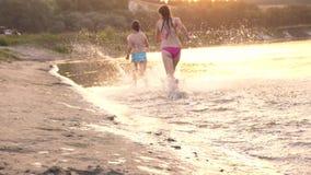 Crianças felizes que correm ao longo da praia As meninas correm na areia ao longo da costa na praia que espirra gotas e riso da á
