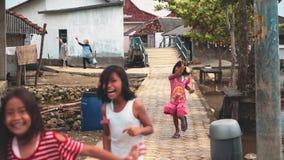 Crianças felizes que correm através da vila vídeos de arquivo