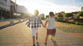 Crianças felizes que correm unidas manter as mãos na estrada Os raios do sol brilham em suas caras filme