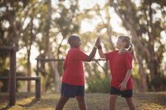 Crianças felizes que dão a elevação cinco durante o curso de obstáculo foto de stock