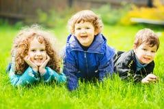 Crianças felizes que encontram-se na grama e no sorriso fotos de stock royalty free