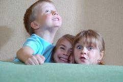 Crianças felizes que escondem atrás do sofá Fotografia de Stock