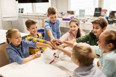 Crianças felizes que guardam as mãos na escola da robótica fotos de stock
