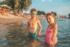 Crianças felizes que guardam as mãos no mar foto de stock royalty free
