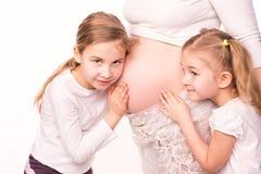 Crianças felizes que guardam a barriga da mulher gravida Fotografia de Stock Royalty Free