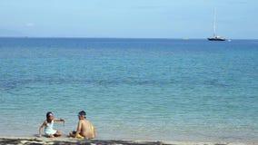 Crianças felizes que jogam a areia na praia filme