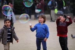 Crianças felizes que jogam com bolhas de sabão Imagens de Stock