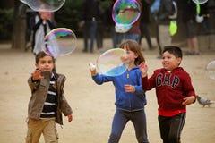 Crianças felizes que jogam com bolhas de sabão Fotografia de Stock