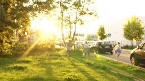 Crianças felizes que jogam em um parque da cidade Brilho do sol de ajuste, coelho ensolarado, conceito feliz da infância, os jogo video estoque