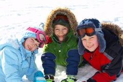 Crianças felizes que jogam na neve imagens de stock