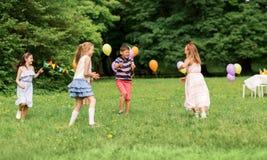 Crianças felizes que jogam o jogo da etiqueta na festa de anos Fotos de Stock