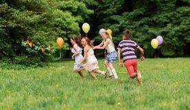 Crianças felizes que jogam o jogo da etiqueta na festa de anos Imagem de Stock