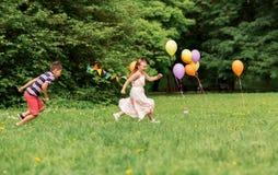 Crianças felizes que jogam o jogo da etiqueta na festa de anos Imagens de Stock