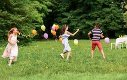 Crianças felizes que jogam o jogo da etiqueta na festa de anos Fotografia de Stock Royalty Free