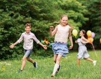 Crianças felizes que jogam o jogo da etiqueta na festa de anos Foto de Stock
