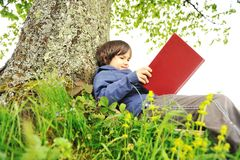 Crianças felizes que lêem o livro Imagem de Stock