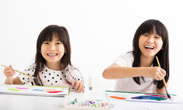 Crianças felizes que pintam na sala de aula Imagem de Stock