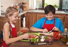Crianças felizes que preparam uma pizza junto Foto de Stock Royalty Free