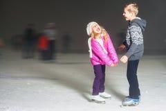 Crianças felizes que riem da pista de gelo exterior, patinagem no gelo Fotografia de Stock