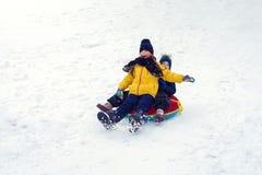 Crianças felizes que sledding a tubulação jogo do irmão e da irmã junto no inverno as crianças deslizam para baixo o monte as cri fotografia de stock royalty free