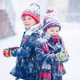 Crianças felizes que têm o divertimento com neve no inverno Imagem de Stock Royalty Free