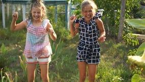Crianças felizes que têm o divertimento em um dia de verão ensolarado em uma vila no jardim que salta sob os jatos da água de uma vídeos de arquivo