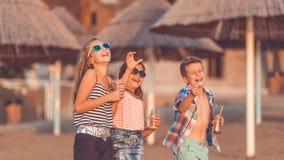 Crian?as felizes que t?m o divertimento na praia no tempo do dia imagem de stock royalty free