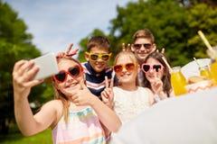 Crianças felizes que tomam o selfie na festa de anos fotografia de stock royalty free
