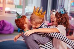 Crianças felizes que vestem as coroas de papel durante o partido fotografia de stock royalty free