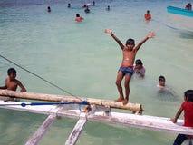 Crianças filipinas que jogam e que nadam na praia Imagens de Stock