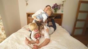 Crianças impertinentes da família com escalada da mãe no pai para trás na cama Tiro Handheld filme