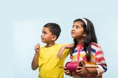 2 crianças indianas que voam o papagaio, uma que guarda spindal ou chakri Imagem de Stock