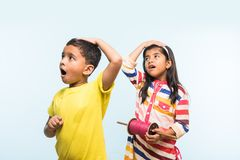 2 crianças indianas que voam o papagaio, uma que guarda spindal ou chakri Imagens de Stock