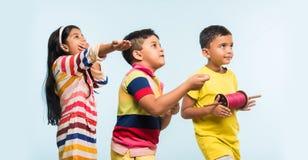 3 crianças indianas que voam o papagaio, uma que guarda spindal ou chakri Imagens de Stock