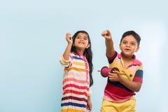 2 crianças indianas que voam o papagaio, uma que guarda spindal ou chakri Fotos de Stock